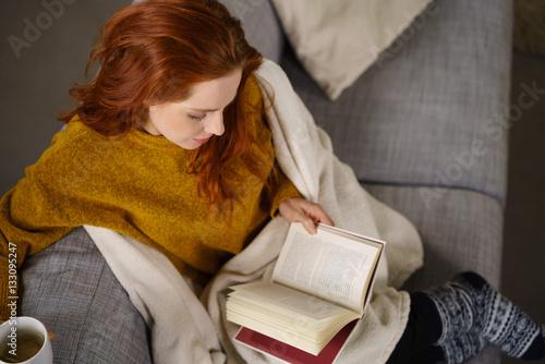 zrelaksowana kobieta czyta książkę na kanapie
