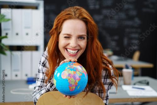 Foto Murales frau zeigt einen globus und zwinkert mit einem auge