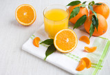 Fresh orange juice in a glass on a background of fruit baskets
