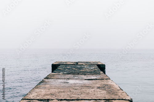 Old wet concrete pier on a cloudy day - 133103070