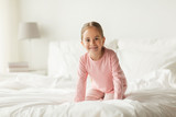 happy little girl on bed at home bedroom
