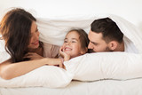 happy family lying in bed under blanket at home