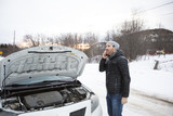 man on the winter road is calling the phone near the car