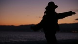 Silhouette of a Dancing Girl on the Beach at the Sunset