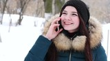 4k UltraHD video of young nice girl speaking by mobile phone in winter park.