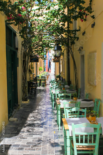 Poster Tables and chairs of cafe are on the narrow street of Rethymnon (part of Old Tow