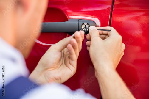 Poster Person Opening Car Door With Lockpicker