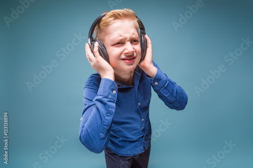 Poster Teenager in headphones with a sour face listening to music