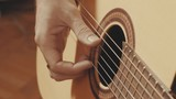 Hands of guitarist slowly plucking the strings of guitar