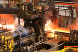 Hot steel being rolled to shape in mill in steel manufacturing plant.