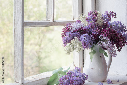 Foto op Canvas Lilac blooming branch of lilac at the window