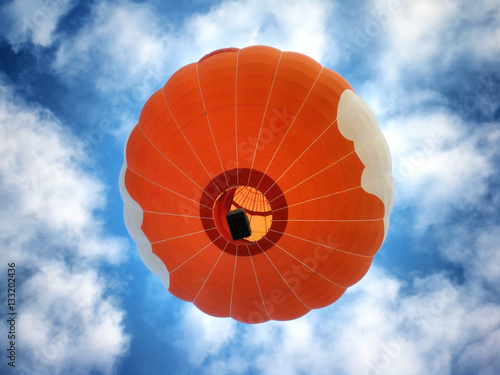 Deurstickers Ballon Orange hot air balloon from the bottom on the background of blue sky.
