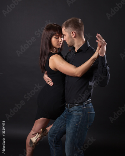 Young couple dancing on a dark background - 133204078