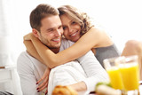 Fototapety Young couple eating breakfast in bed