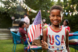 Young black boy holding flag at 4th July family garden party - 133220016