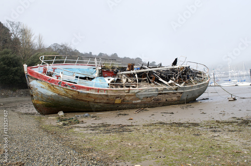 Keuken foto achterwand Schip Burnt out ship wreck, boat fire damage, beached on coast shore line, fishing motor boat