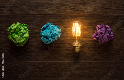Poster Great idea concept. Shining lightbulb between crumpled paper she