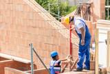 Bauarbeiter bauen Haus auf Baustelle - 133315805