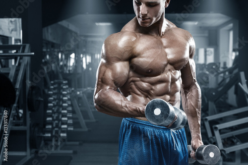 Muscular man working out in gym doing exercises with dumbbells, bodybuilder male Poster