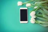 White mobile phone and bouquet of tulips