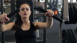 In the gym beautiful woman performs a bench press from the chest.