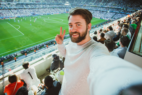 Handsome bearded man watching football game and making selfie self-portrait with smartphone at Camp Nou Stadium in Barcelona, Spain