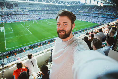 Poster Handsome bearded man watching football game and making selfie self-portrait with