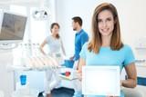 Happy dental assistant holding tablet