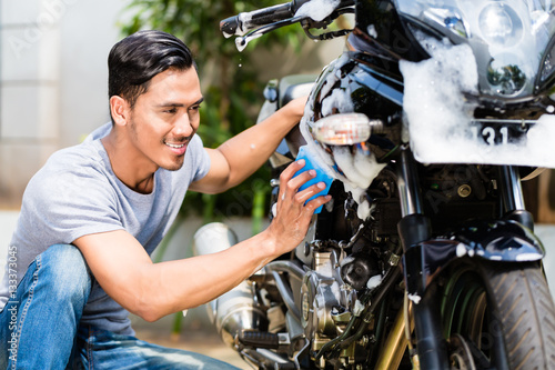 Poster Asian man washing his motorcycle or scooter