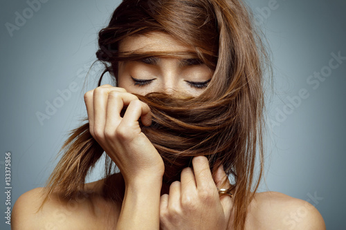 Beauty portrait of young woman with long hair over the face