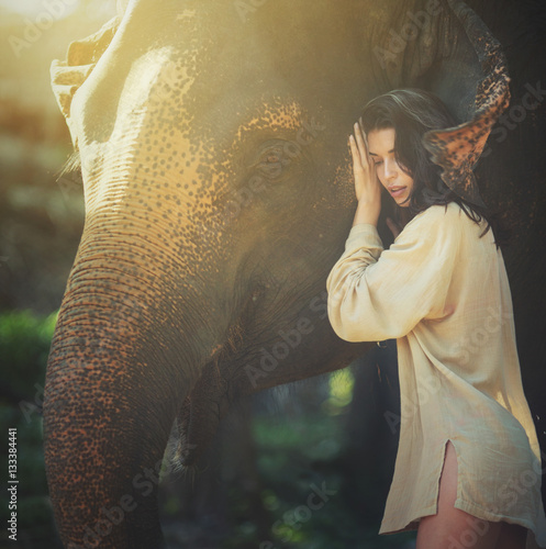Poster beautiful young woman posing with happy elephant