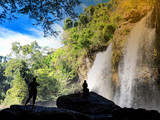 traveler standing at waterfall in deep forest at Khao Yai Nation