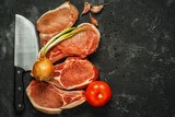 Four large raw pork steaks on the black background with knife, garlic, onion and pepper. Copy space for your inscription.