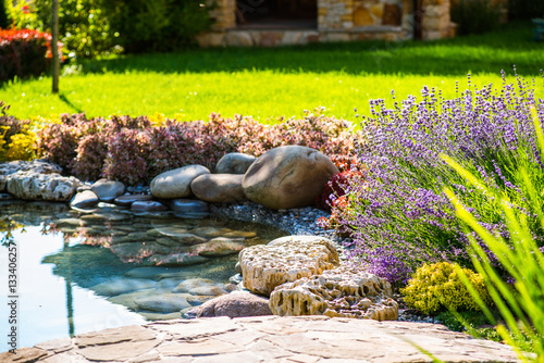 Beautiful backyard landscape design. View of colorful trees and decorative trimmed bushes and rocks - 133406257