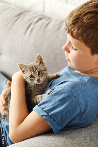 Poster Child with kitten on grey sofa at home
