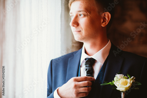Poster portrait of a young groom standing near window