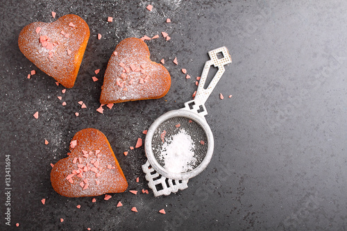 Poster cupcakes in heart with powdered sugar on a black background