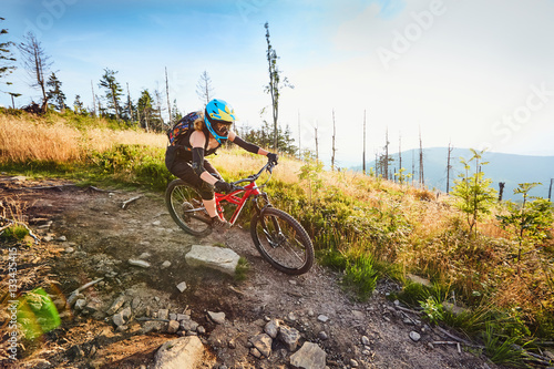 Deurstickers Fietsen female mountain biker riding downhill on MTB bike