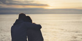 Fototapety Couple hugging on the beach on background ocean sunrise, silhouette two romantic people cuddling and looking on rear view evening seascape, hipster enjoy  sunset together, travel holidays vacation