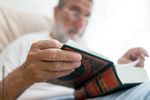 Senior Arabic man reading book Poster