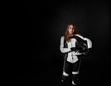 Fototapety Extreme young girl with red hair in protection body armor of motorcycle sport with helmet in hands. Tired woman after the race on black background with copy space for advertising text.