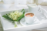 Delicious espresso with flowers on white table