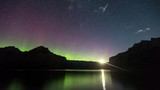 View of the Sunrise on the Background of the Northern Lights . View of the Mountains That Stretched Around the Lake.