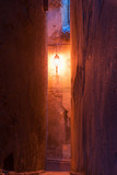 Warm glow of single street light at end of small French town narrow lane