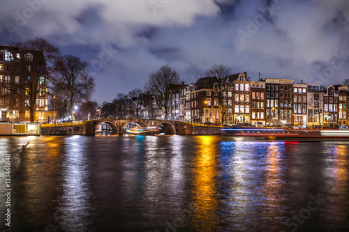 Poster AMSTERDAM, NETHERLANDS - JANUARY 12, 2017: Beautiful night city canals of Amsterdam with moving passanger boat