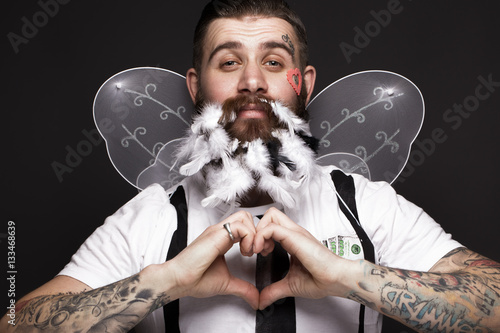 Funny bearded man with feathers and wings in the image of Cupid Valentine's Day. Portrait shot in studio