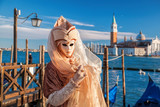 Famous carnival mask against gondolas in Venice, Italy - 133475023