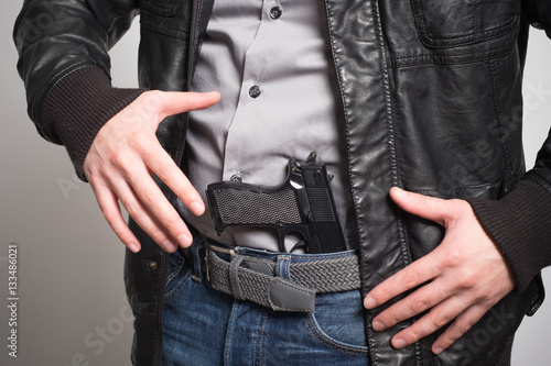 Man pulling out a gun ready to shoot Poster