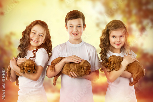 Poster Three cute children with puppys outdoor. Kid pet friendship