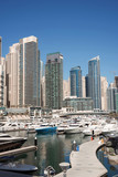 Dubai harbor with boats and yachts on a mooring, on skyscrapers background, vertical